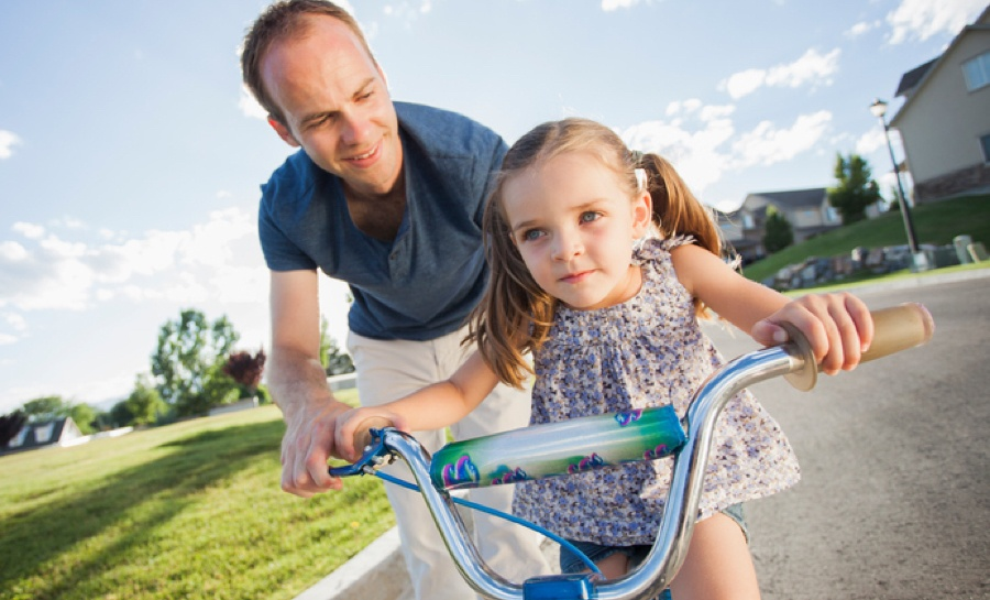 This is a photo of a father and his daughter, who is beginning to ride a bike. The image symbolizes the target market of a life insurance business that HawkPartners developed a go-to-market plan to reboot the business's efforts.