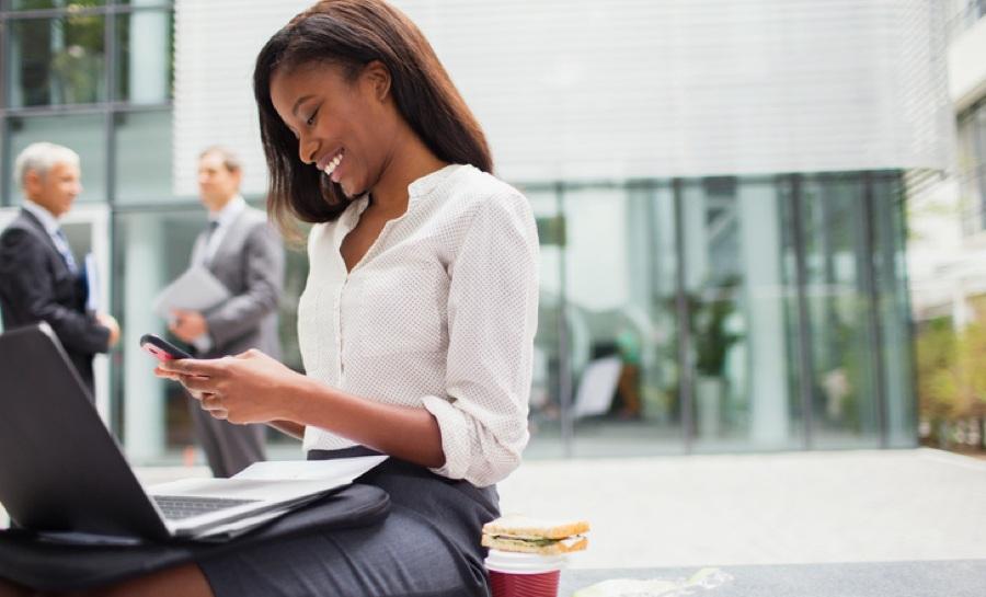 This is a photo of a woman working on-the-go engaging with her phone. The image symbolizes a user engaging with the digital content platform HawkPartners improved after conducting interviews and focus groups about how users would use the app.
