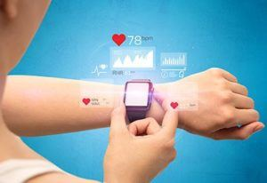 Pictured: a woman is interacting with a smart watch. Displayed above it are holograms of health information, like heart BPM.