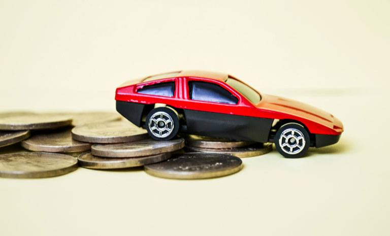 This is a photo of a toy car sitting on top of coins. The image symbolizes the customer journey map HawkPartners created to give an auto lender a better understanding the customer path-to-purchase.