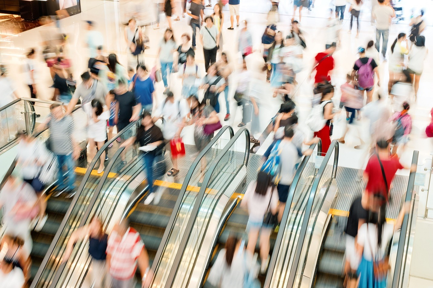This is a time-lapse photo of shoppers going up and down a mall escalator. The image symbolizes segmenting consumer markets.