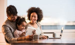 Pictured: a couple with their child sitting at a table, using a laptop and a tablet. The image is a metaphor for designing multi-user programs and associated platforms to grow customer relationships.