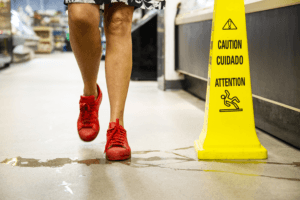 A shopper walking through an aisle, about to step on spilled liquid. There is a caution sign, but it is unnoticed. The image is a metaphor for designing a poor customer experience.