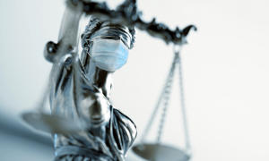 A statue with a mask holding the scales of justice. It is a metaphor for holding a jury trial during COVID-19.